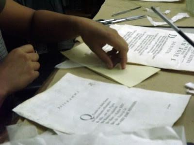 mãos restaurando folhas de um livro