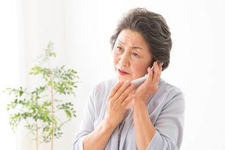 耳が遠く、電話の音が聞き取りにくく困っている女性のイメージ