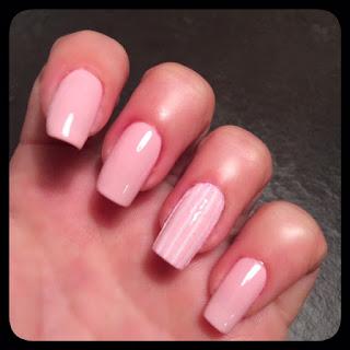 Nail art rosa chiaro, ricreata con le strisce di filo decorativo per ottenere un risultato a strisce rosa e bianche.