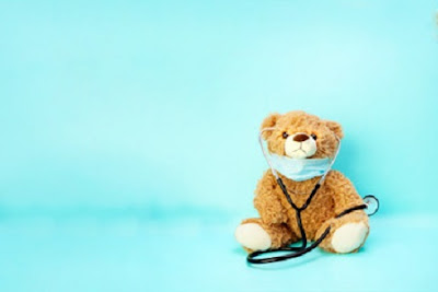 Cuddly bear wearing a surgical mask and stethoscope