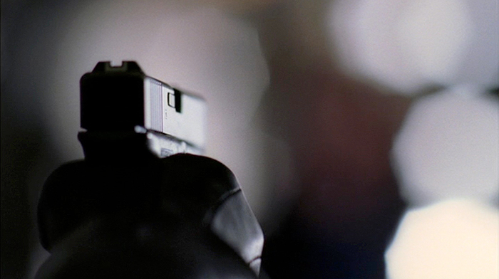 Pistola empuñada por un asesino que no se ve, apuntando a un fondo distorsionado.