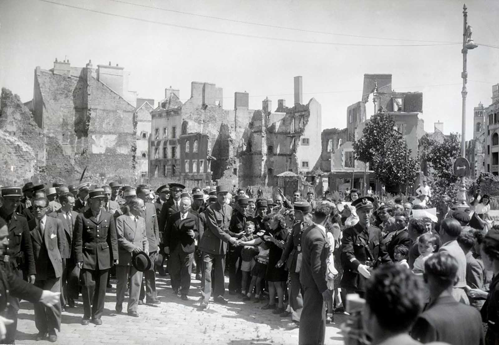 General Charles de Gaulle (center) shaking hands with children, two months after the German capitulation in Lorient, France, in July of 1945. Lorient was the location of a German U-boat (submarine) base during World War II. Between January 14 and February 17, 1943, as many as 500 high-explosive aerial bombs and more than 60,000 incendiary bombs were dropped on Lorient. The city was almost completely destroyed, with nearly 90% of the city flattened.