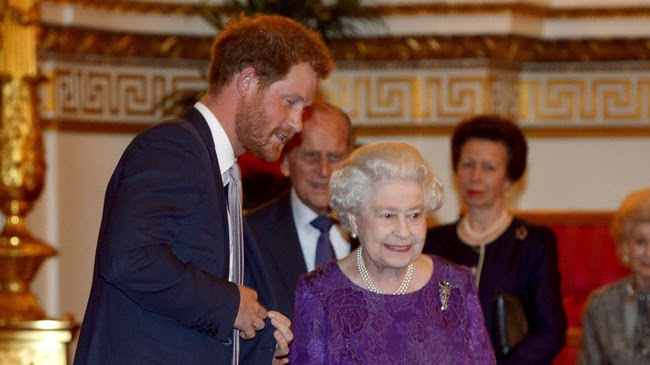 Britain's Prince Harry and Queen Elizabeth look at the Webb Ellis Cup on a plinth during a Rugby World Cup reception at Buckingham Palace, London October 12, 2015.