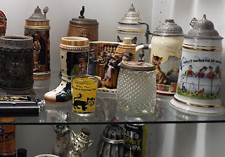 Several beer steins and other glassware, all with cats on them. American Museum of the House Cat.