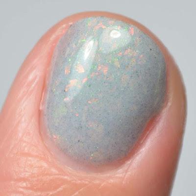 grey nail polish with flakies close up swatch