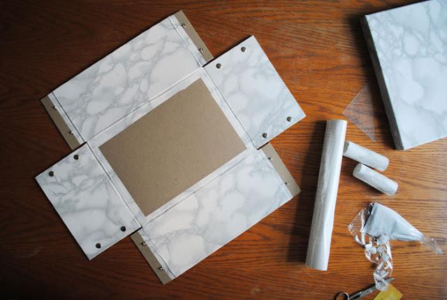 Uitgevouwen kartonnen doos met marmer plakplastic aan de zijden