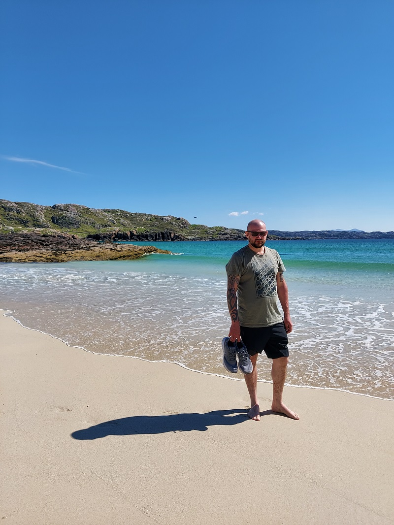 Gordon in shorts and shades on a beautiful day at Oldshoremore beach, with helicopter in background