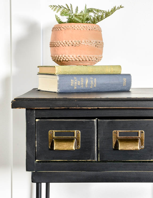 Black painted side table with metal label holders