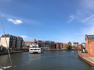 waterway with buildings either side under a clear blue sky