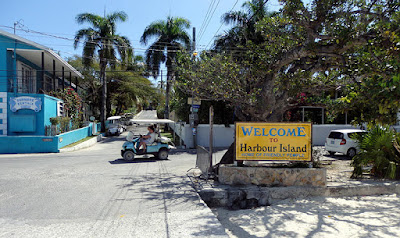 Welcome to Harbour Island sign and golf cart on street.