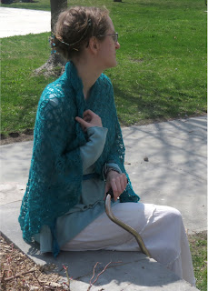 A woman sitting on a concrete edge; wearing a large blue-green lace shawl. She is holding the shawl at her neck with one hand. There is a cane in her other hand.