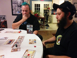 Two players contemplating their next move at Harbour. Both are sitting at a table looking at the components of Harbour, which are spread out before them.