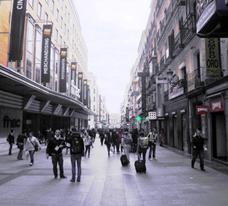 La calle en ligera pendiente hacia la Puerta del Sol. Destacan los anuncios de tiendas y almacenes comerciales.