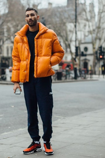 Men's street style: orange puff jacket with pants and orange tennis shoes