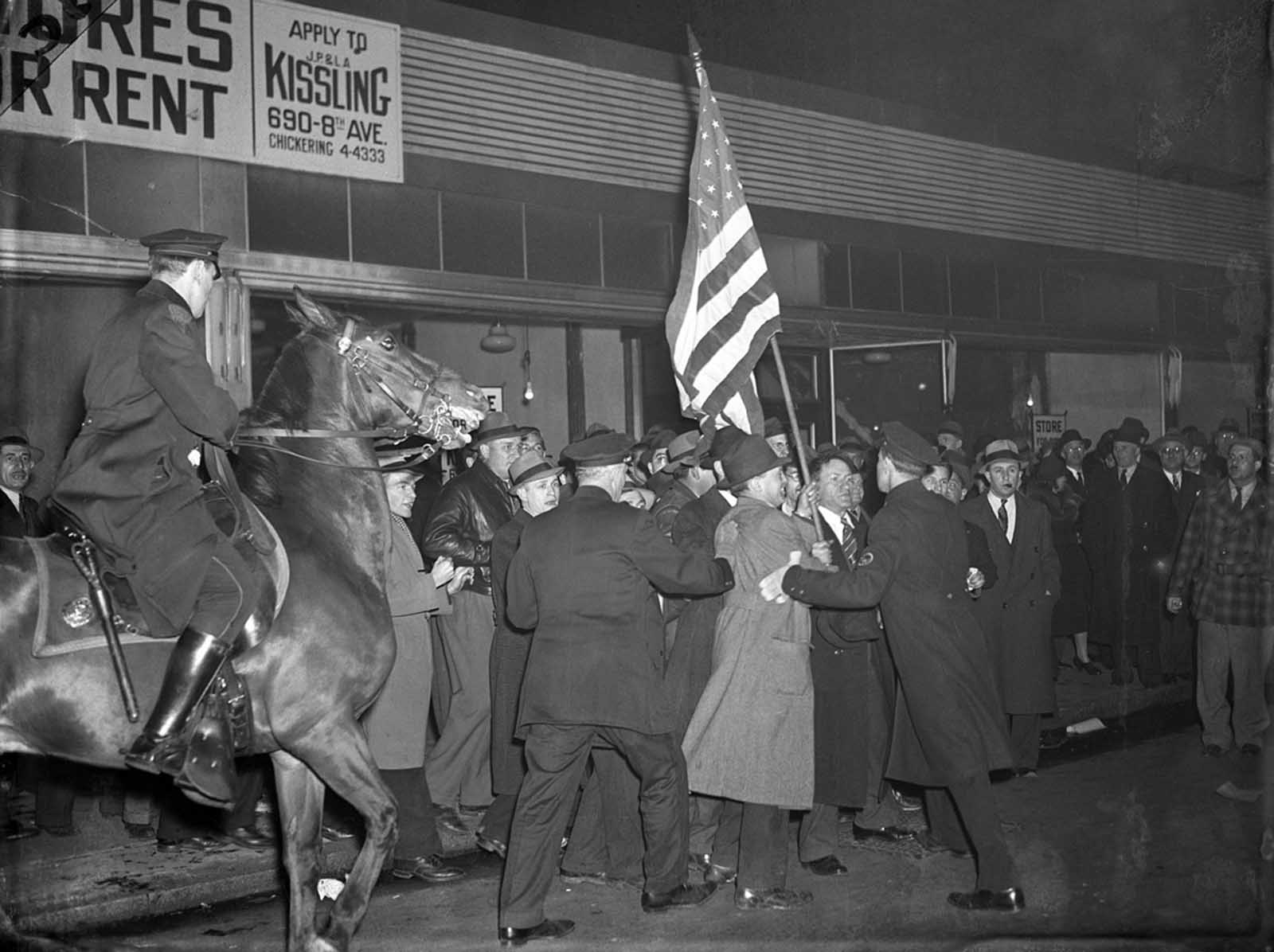 February 20, 1939. Original Caption: Fight For The Flag... Anti Nazis Battle Cops. Mounted Policemen and rabid Anti Nazis battle for an American flag outside Madison Square Garden. The Anti-Nazis were parading outside the Garden in protest of the German American Bund