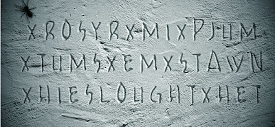Figure: Figure: You're in! You hear a voice whispering your name. In a daze, you follow it up the spiral staircase into the lantern room. It's empty. You step outside to the gallery and notice a message carved on the wall. It's Martha's handwriting! You must decipher the code! What is she trying to tell you?