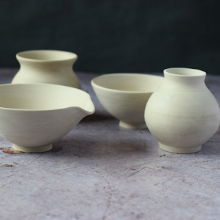 Greenware bowls, containers and a bud vase about to be fired.
