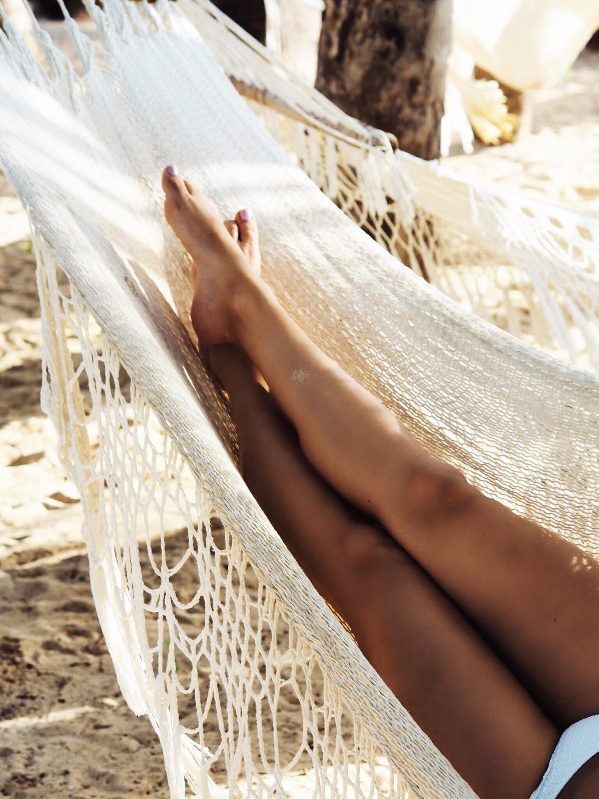 Tanned Legs in Woven Hammock with Sand underneath