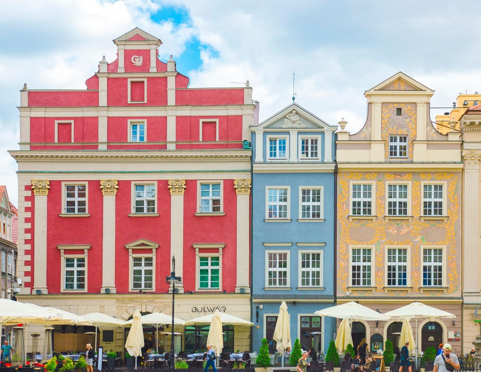 Trzy stykające się ze sobą kamieniczki w renesansowym stylu. Pierwsza od prawej czerwona, środkowa mniejsza w kolorze błękitu i ostatnia po prawej w kolorze pomarańczy ze złotymi zdobieniami. Okna ozdobione portalami w stylu klasycystycznym. Fasady wykończone kolumnami w porządku korynckim.