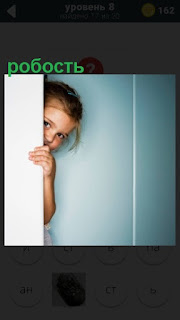 робкая девочка спряталась за дверью и выглядывает