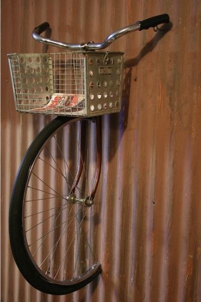 Sepeda yang ditanam di dinding. Keranjang sepedanya bisa jadi rak yang unik. Aku suka efek yang membuat seolah-olah sepeda ini ditelan dinding.