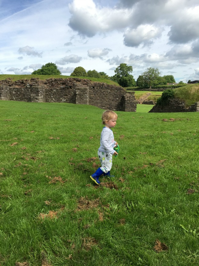 Caerleon-the-roman-fortress-of-isca-a-toddler-walking-on-grass
