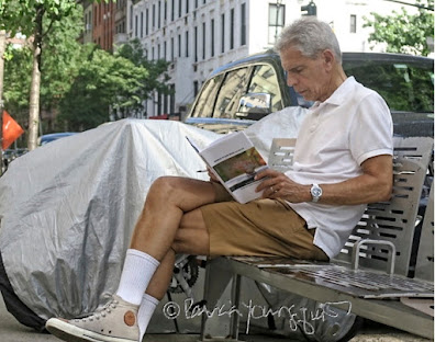 "A white-haired man in his late sixties, dressed in caramel-colored shorts and a white short sleeved polo shirt is sitting on a silver-colored metal bench (located on a street in Manhattan's UWS) reading volume one of my book series (""Words In Our Beak""). Information re this book as well as info re volumes two and three is on my blog @ https://www.thelastleafgardener.com/2018/10/one-sheet-book-series-info.html"