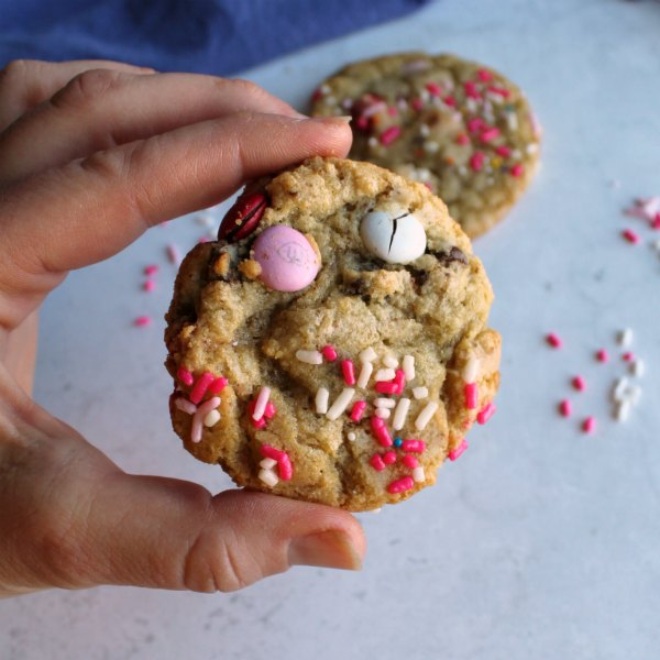 hand holding M&M cookie with some Valentine's sprinkles on top