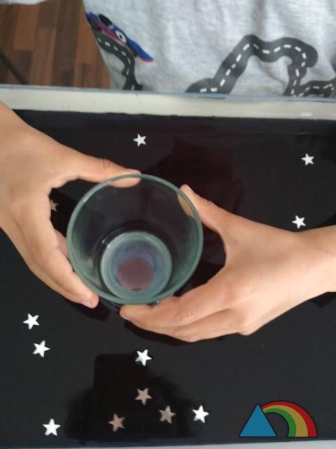 Niño buscando planetas en una bandeja transparente con agua negra, con la ayuda de un vaso