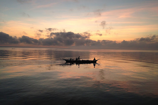 a fishing canoe on the water at sunset