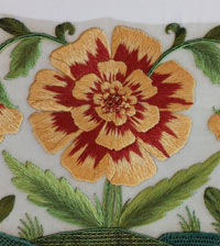 yellow flower with a red centre and several green shaded leaves, stitched with long and short stitch
