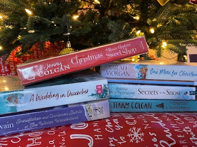 Large pile of Christmas books under the Christmas tree
