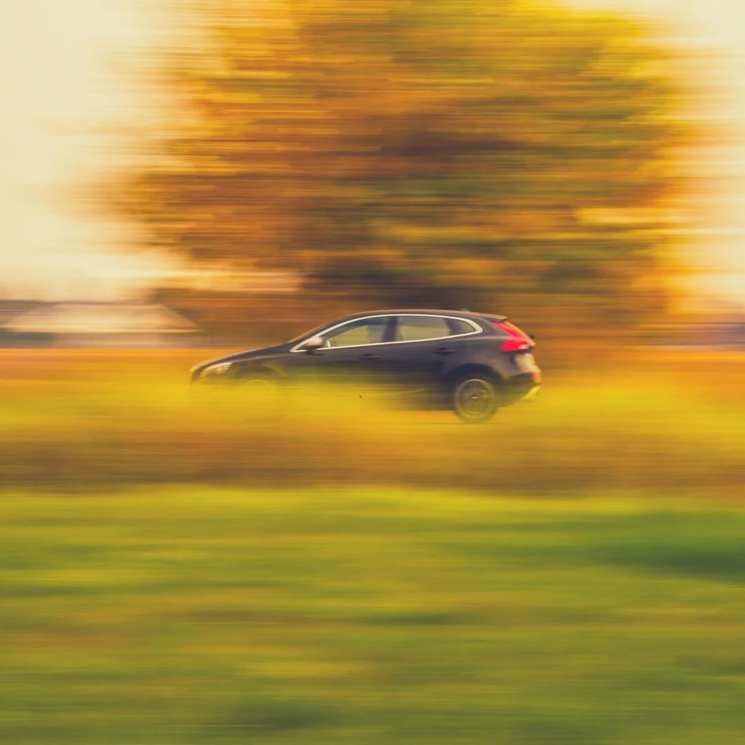 A car drives along a road, there's a blurred tree in the background and blurred grass in the foreground, indicating the car is travelling.
