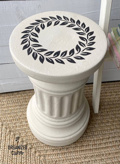 Photo of off white painted terracotta pedestal with black wreath stencil