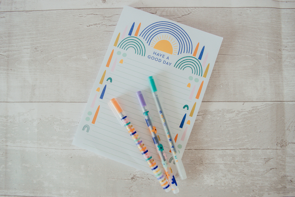 Three gel pens laid on a notepad