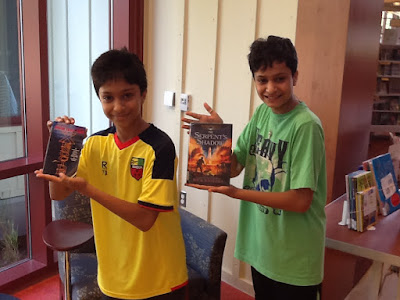 Brothers Pratham and Arnav holding up their favorite summer books