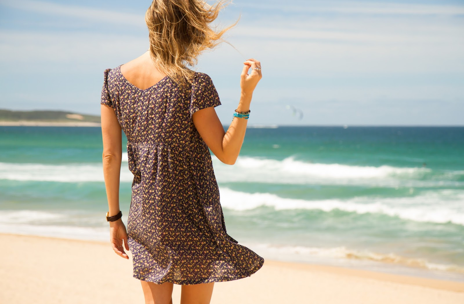 fashion and travel blogger, alison hutchinson, is wearing a floral ralph lauren dress at wanda beach in sydney, australia