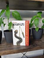 Uskomattomia uhrauksia -kirja parvekkeella ulkohyllyssä, taustalla paprikakasveja ruukuissa