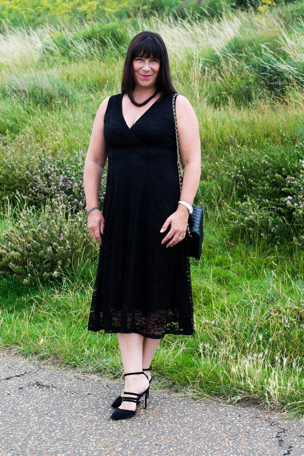 Wearing a black lace dress and high heels, Mummabstylish over 50s fashion blogger