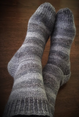 Socks knitted with DROPS Fabel in Silver Fox on feet