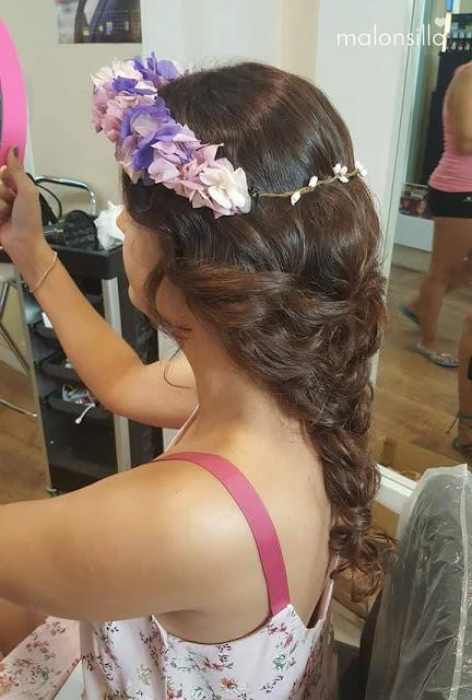 Peinado de la invitada a boda en la peluquería con trenza y corona de flores preservadas.