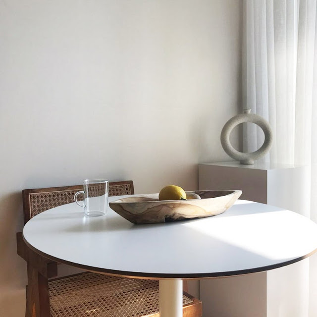 modern donut vase in dining room corner with vintage style table and cane chairs