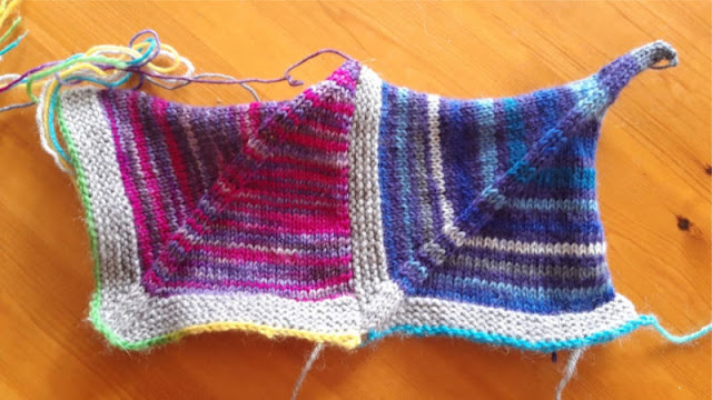 Image shows two coloured knitted blanket squares.  The one on the left is pink and the one of the right is blue.  They are both made from leftover sock yarn