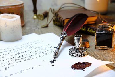 Escritura. Mesa con papel escrito, pluma, tintero, vela, libros antiguos y posa pluma.
