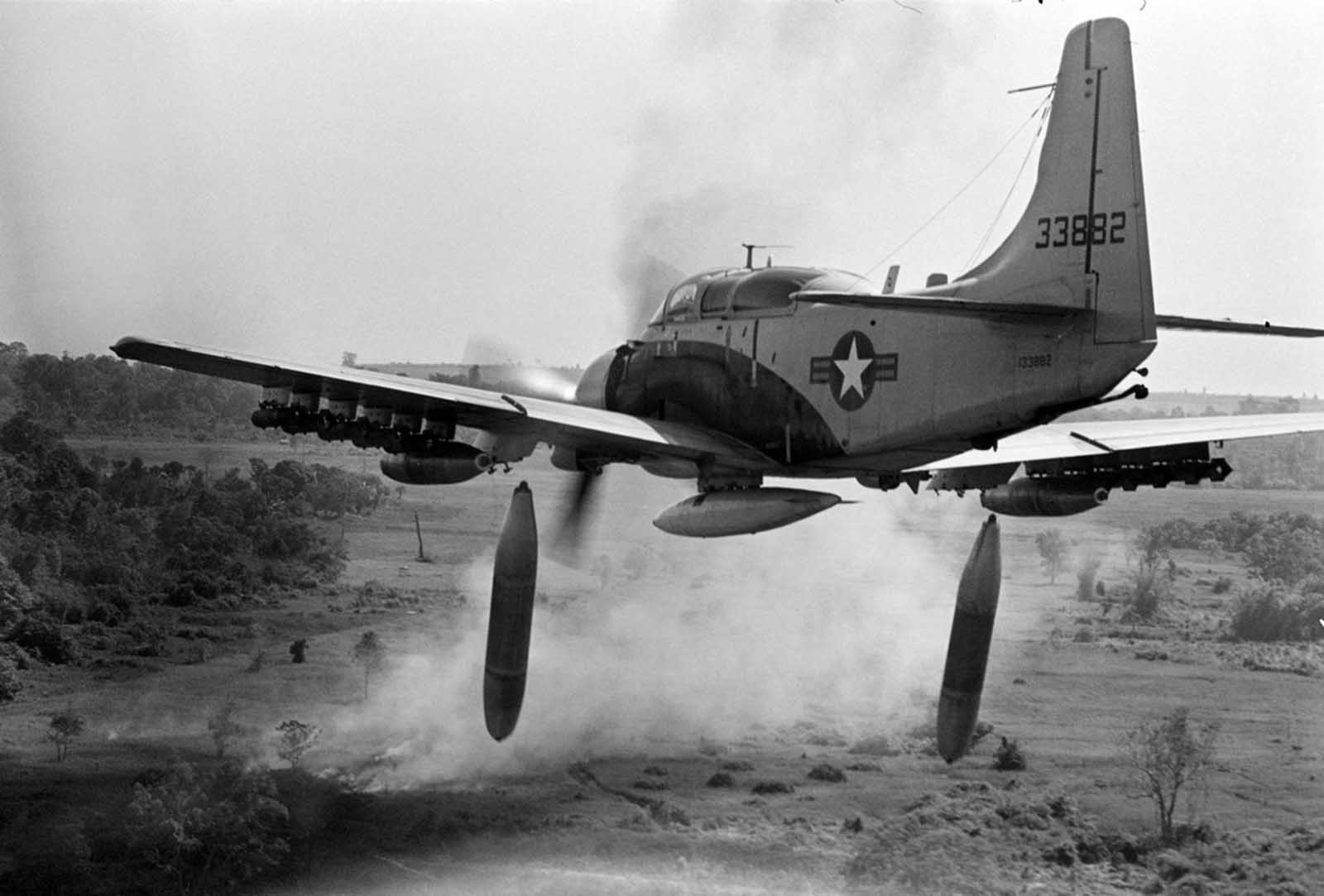 Flying low over the jungle, an A-1 Skyraider drops 500-pound bombs on a Viet Cong position below as smoke rises from a previous pass at the target, on December 26, 1964.