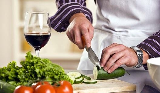 Homem cortando legumes sobre uma tábua de mesa