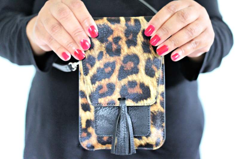 a woman holding a leopard purse
