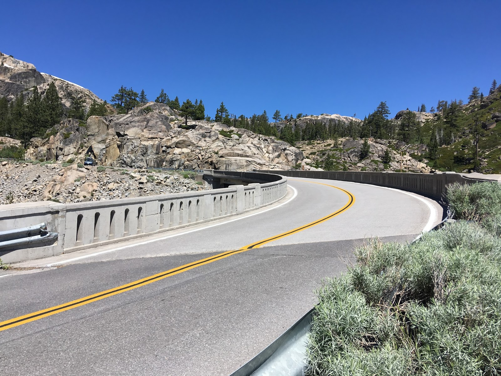 the final climb over the rainbow bridge to donner pass narrows slightly donner pass is signed at 7 135 feet above sea level