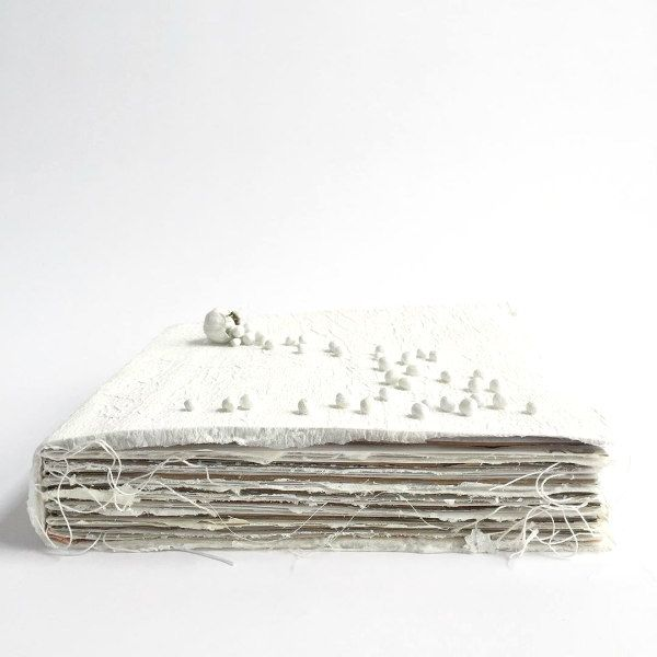 white handmade artist book with loose threads - side view