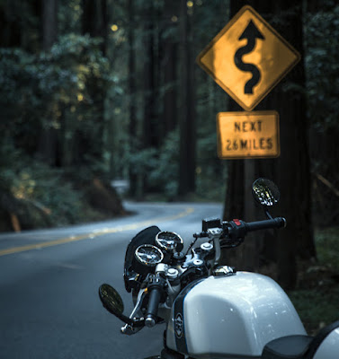 "Motorcycle parked under ""Curves Next 26 Miles"" sign."